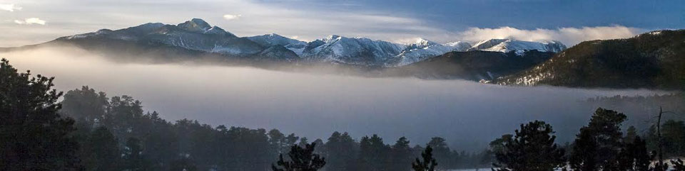 Photo of early morning clouds hanging low in the valley with mountains of the Continental Divide stretched out above. NPS Photo/Schonlau