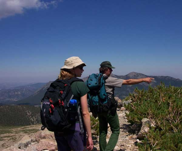 a photo of ranger viewing historic resources on Longs Peak trail