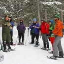A ranger and teachers snowshoe in the park