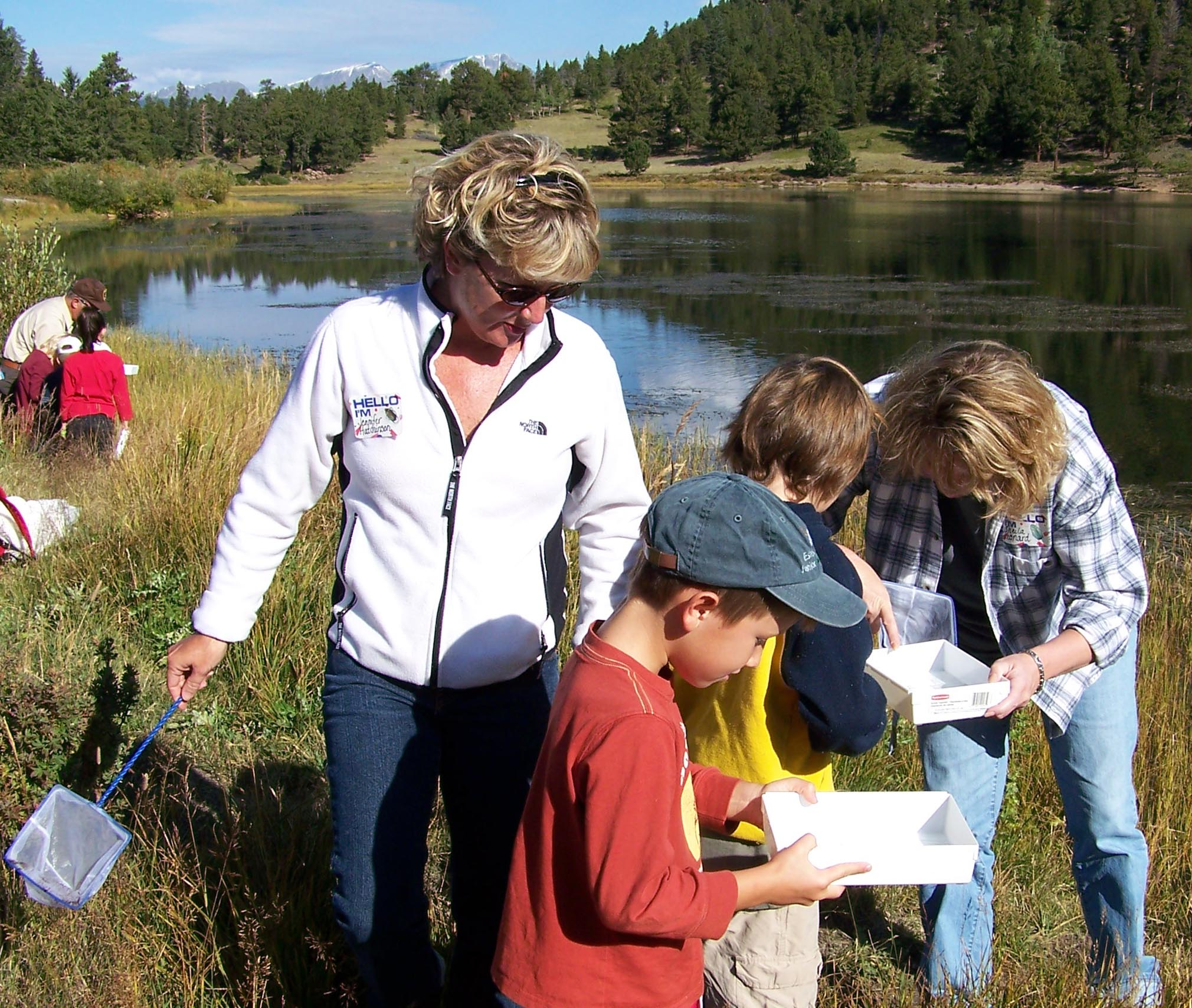 Teachers assist students exploring nature.