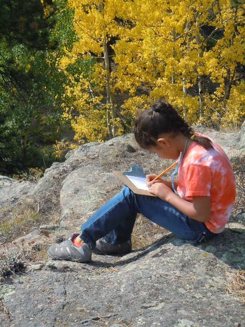 young student sitting on a rock and writing