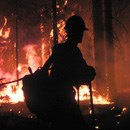 Silhouette of a firefighter by a fire