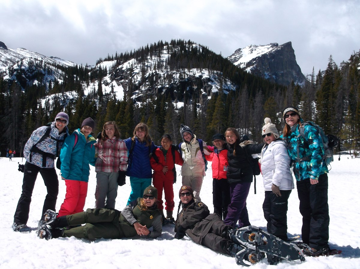 A group of girl scouts and 2 rangers standing on a frozen lake with mountains in the background