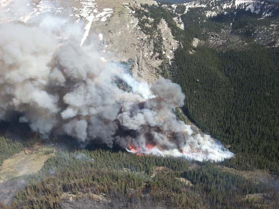 Photo of firefighters using an existing avalanche chute as a natural barrier to perform a burn out operation on June 14, 2013.