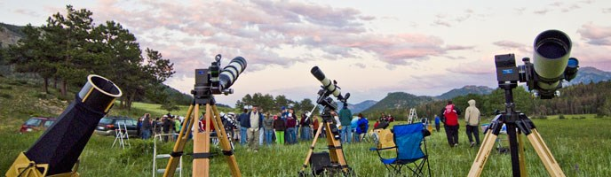 telescopes and people in a meadow