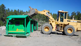 Photo park staff use a front loader to deposit beetle-killed trees into the park's air curtain burner.