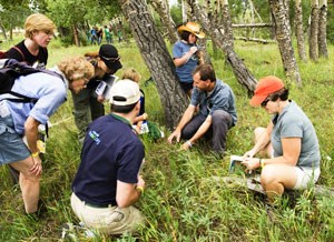 A scientist inventories vegetation with participants