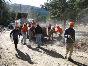 Photo park volunteers feed beetle-killed trees into the chipper.