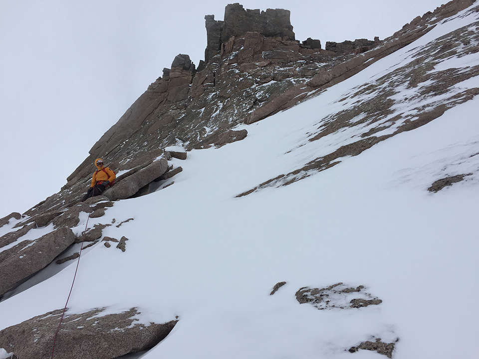 A climbing ranger, rope attached, sits on snow and ice on Longs Peak