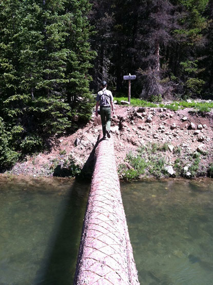 Backcountry Ranger hiking over a footbridge in Rocky Mountain National Park.