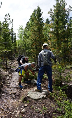 Three volunteers work to move a branch off trail.