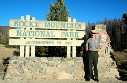 Photo Ranger Andrew standing in front of official Rocky Mountain National Park sign.