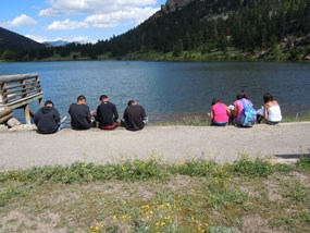 Students sitting on the edge of Lily Lake.