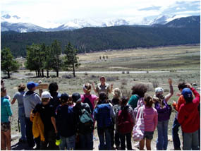 Photo of GeoCorps Environmental Education Intern with a group of students looking at the glacially carved landscape of Moraine Park