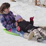 Mom and child sledding at Hidden Valley