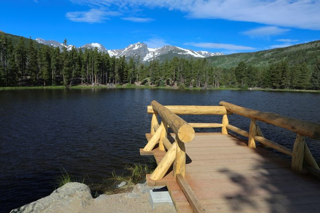 A wooden dock on a lake shore with mountains in the distance.