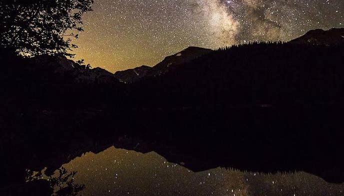 Photo of the milky way stretching over bear lake and reflecting in the still water.