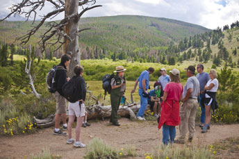 Photo of a park ranger leading a group of people on a guided hike in a green meadow.