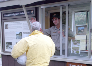 Photo of a park ranger assisting a visitor at Sheep Lakes Information Station.