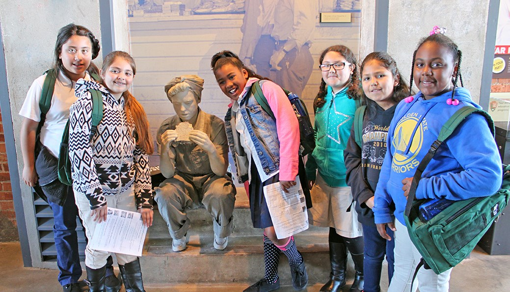 "Young female students are posing with the ""Rosie"" statue."