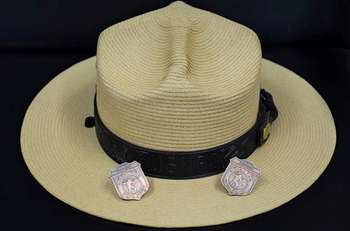 A ranger hat sits with two, metal junior ranger badges standing up on the brim.