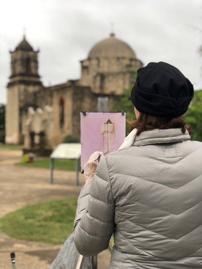 Woman painting Mission San Jose in watercolor while standing in front of her easel at the Mission San Jose church.