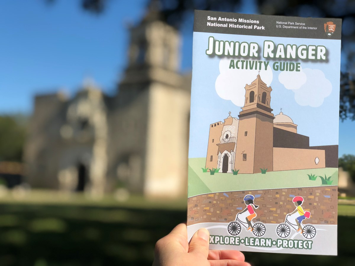 Junior Ranger booklet being held up in front of the church at Mission San Jose