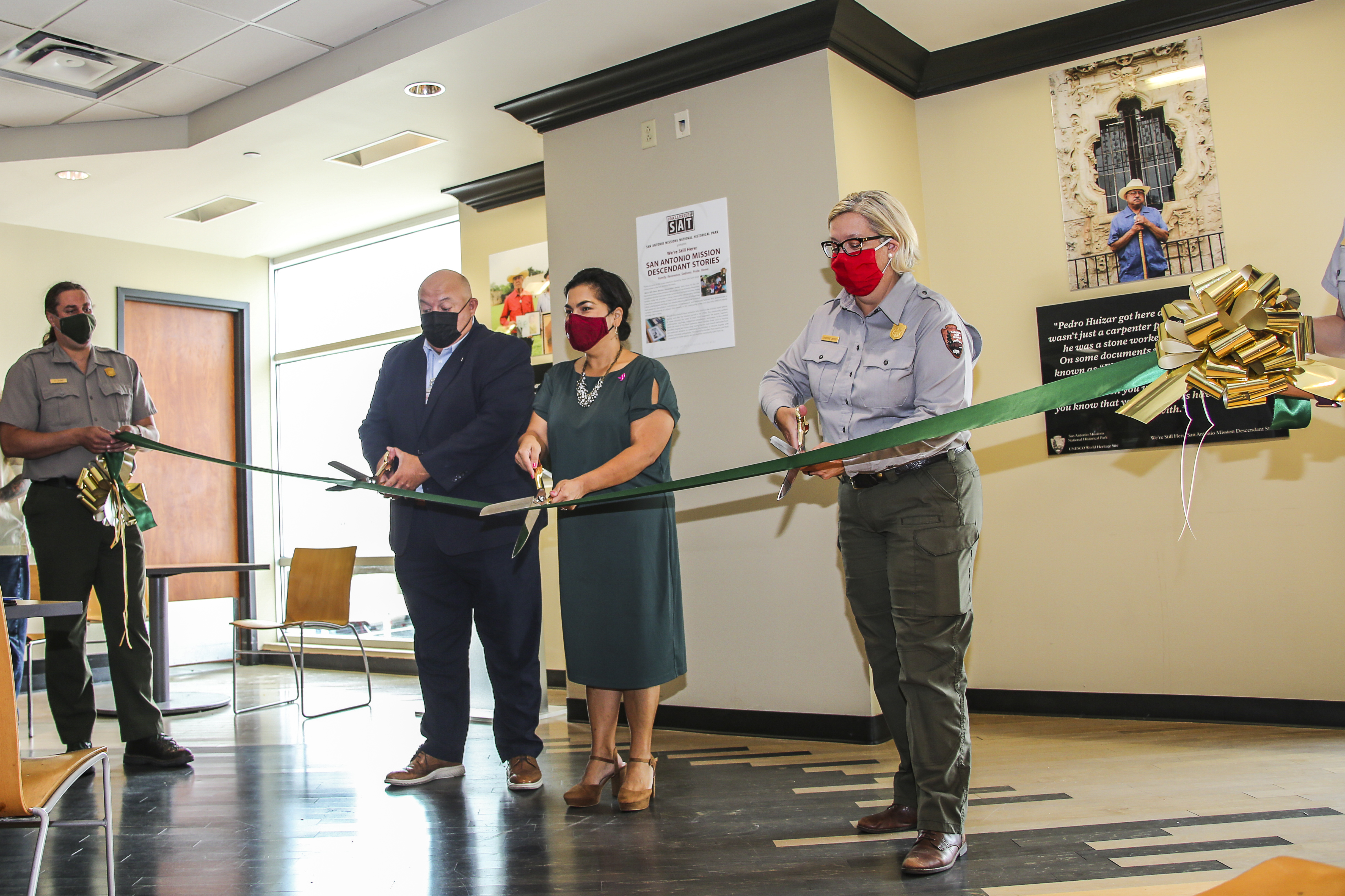 Three officials cutting a large ribbon.