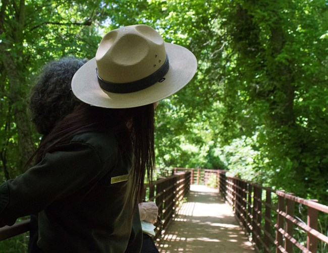 Park Ranger looks down the Yanaguana Trail, where a wooden boardwalk takes visitors along the San Antonio River