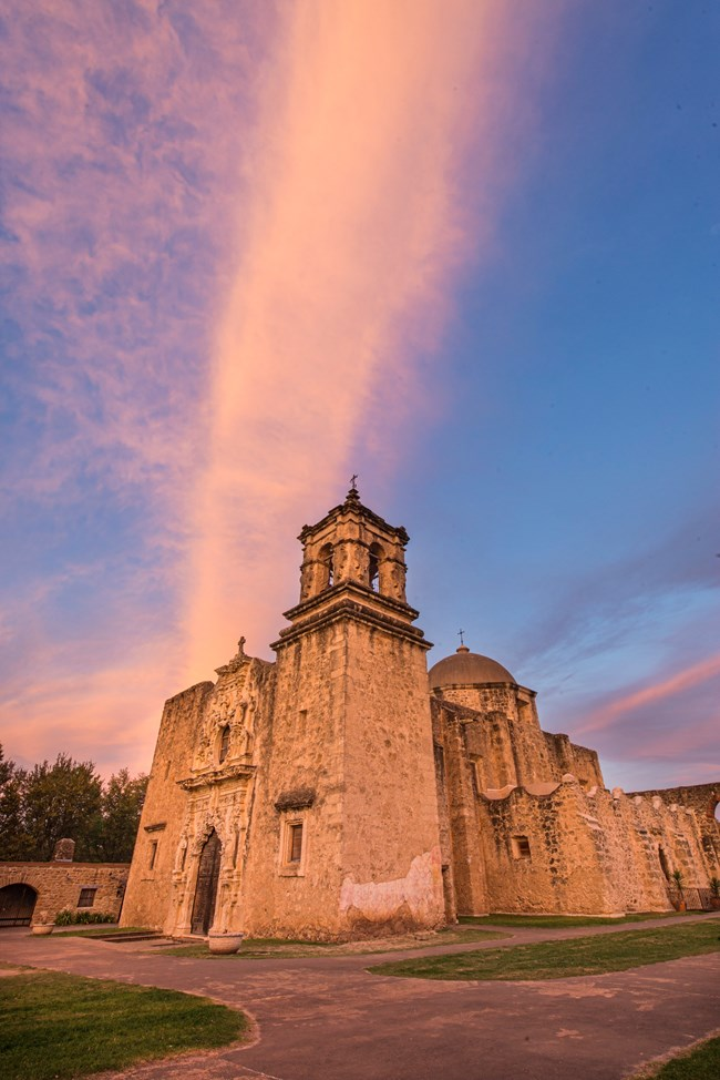 Mission San Jose church and convento buildings against a pink sunset