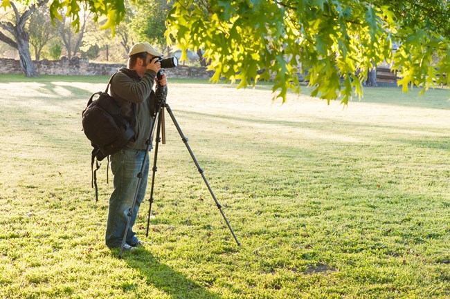 Visitor uses a tall tripod and camera to take photos at the park
