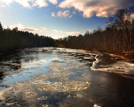 Clouds linger overhead as ice floats on the Namekagon River one recent winter day. Photo by Chris, aged 15