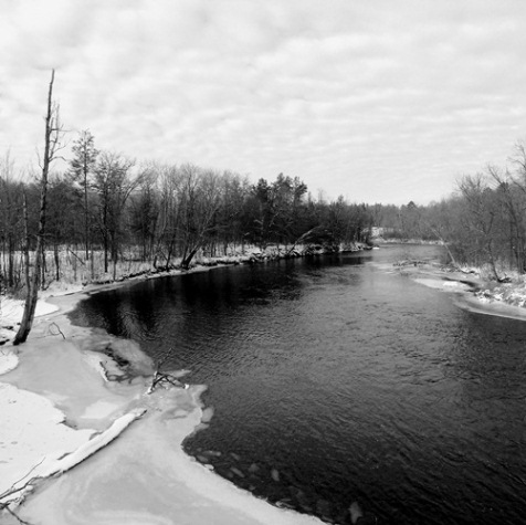 At a bend in the Namekagon River, thin ice lies between open water and a snow covered bank on a recent January day