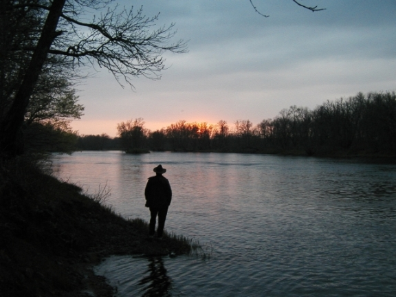 A person stands next to the St. Croix at sunset in spring silhouetted against the moving water and treeline across the river. (NPS Photo)