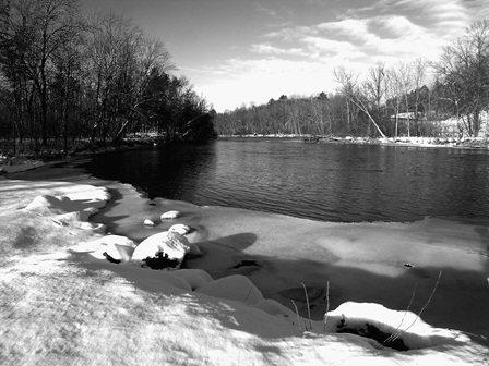 The open waters of the Namekagon River flow around a bend and past a snow covered shoreline.