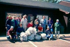 A group of people stand in front of the Trego Visitor Center with bags of trash