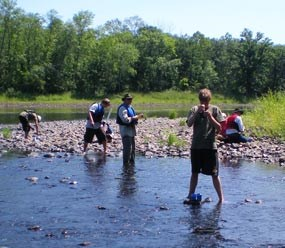 People wading in a shallow river by a rocky river bank, with jars and quizzical expressions