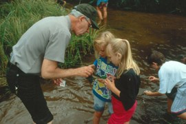 Uniformed ranger with two children looking at aquatic insects they have caught. Third child looking for insects.