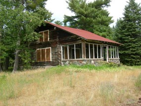 A log 1 1/2 story cabin with red roof and stone porch