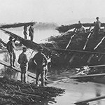 Historic image of men building a wooden structure in water.
