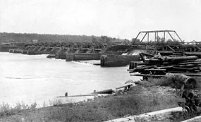 A log dam stretches across the river with many piers and a center gate.  A road runs across the top