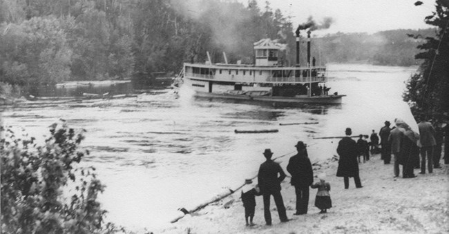 Black and white photo of a steamboat in a river. People standing on shore looking at it.