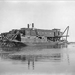 A dredge boat works on a river circa 1910.