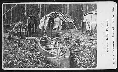 Canoe in frame being built with wigwams in background