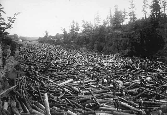 Logs fill the river as far as the eye can see, while men stand on the logs