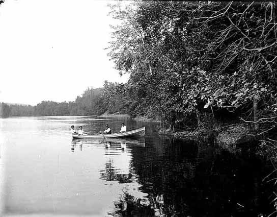 A black and white image of four people in a row boat along tree lined river