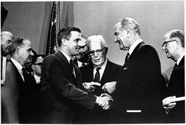 President Johnson hands Senator Mondale a box containing a pen as Chief Justice Earl Warren and others look on.