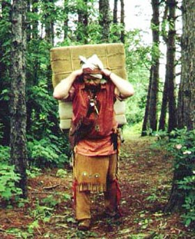 Man dressed in leggings and shirt with sash, walks a trail carrying a large square pack on his back with strap around forehead