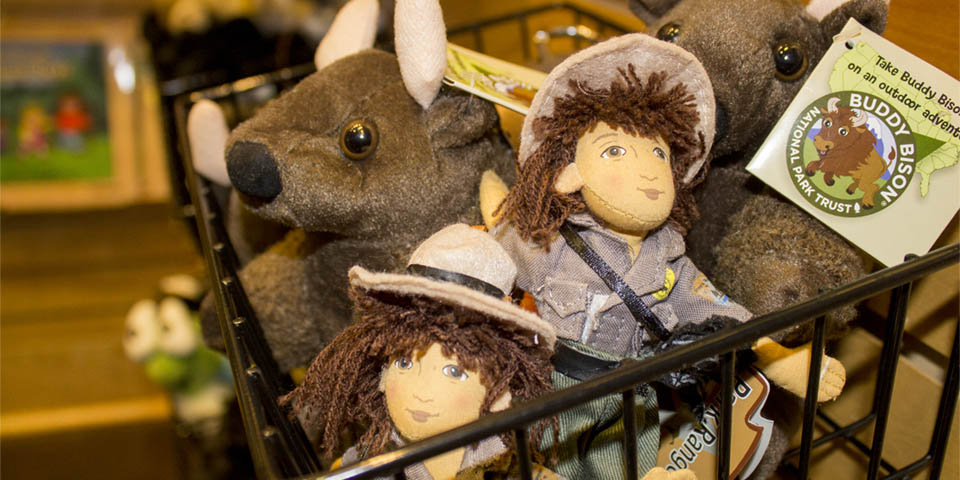 Ranger dolls and stuffed bison peak our from a basket.