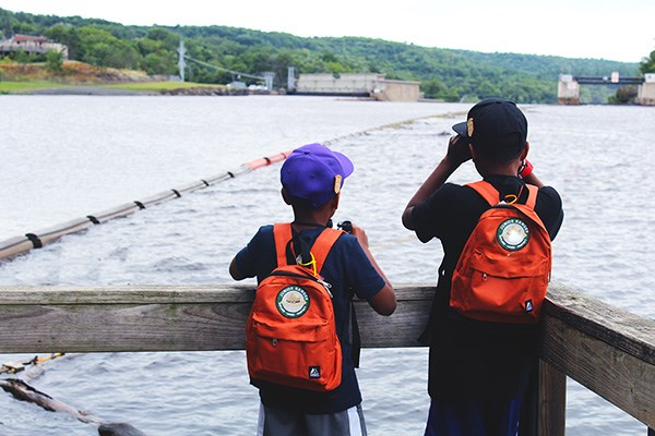 Two young boys using binoculars to look over the St. Croix River.